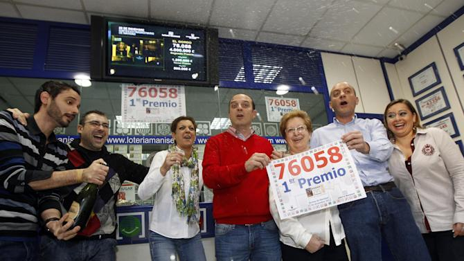 Employees of a lottery outlet celebrate after selling a ticket of the number 76058 corresponding to the Jackpot worth euro 4 million or euro 400,000  for each tenth of the ticket, during the Spanish National Lottery draw,  in Manises, Valencia, eastern Spain,  Saturday Dec. 22, 2012. After a brutal year of economic hardship that deepened with unemployment hitting 25 percent, Spaniards across the country Saturday were hoping for relief from payouts by the nation's famed Christmas lottery, the world's richest, with euro 2.5 billion ($3.3 billion) in tax-free awards.  (AP Photo/Alberto Saiz)