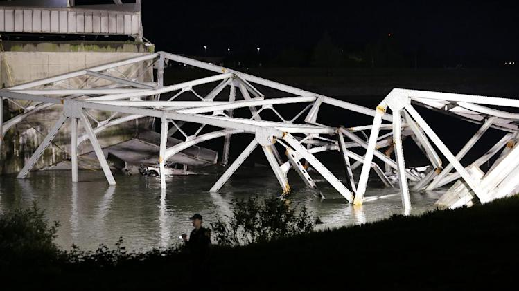 A police officer walks along the bank near the collapsed Interstate-5 bridge submerged after collapsing into the Skagit River, dumping vehicles and people into the water, in Mount Vernon, Wash., Thursday, May 23, 2013. (AP Photo/Elaine Thompson)