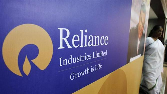 A woman walks past a poster of Reliance Industries installed outside the venue of the company's annual general meeting in Mumbai June 7, 2012. REUTERS/Vivek Prakash/Files
