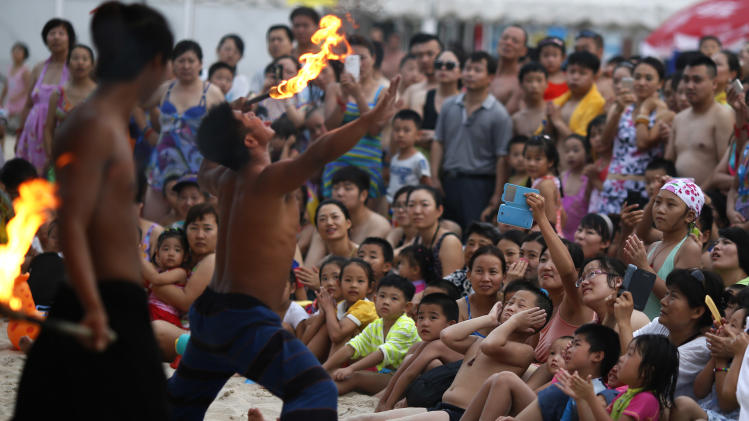 A performer places a burning stick to his tongue during a show for visitors to a beach carnival in Beijing, China, Friday, Aug. 1, 2014. (AP Photo/Ng Han Guan)