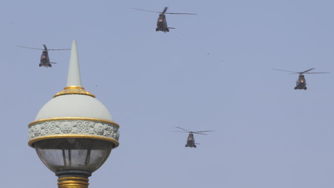Helicopters fly in formation over the Champs Elysees avenue during a Bastille Day celebration in Paris, Sunday, July 14, 2013. (AP Photo/Jacques Brinon)