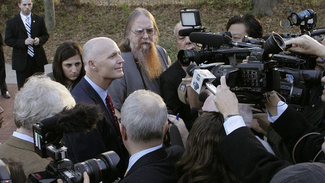 FILE - In this Jan. 31, 2012, file photo Florida Gov. Rick Scott, center left, talks with the media after voting in the Republican presidential primary in Tallahassee, Fla. The Justice Department is opposing changes in Florida voting procedures and says it wants a trial in the dispute, a move that could impact the state's August primary elections. In court papers filed Friday night, March 2, 2012, Florida officials say they strongly oppose having a trial and noted that the federal court hearing the case in Washington wants sufficient time to issue a decision before the August primaries.  (AP Photo/Steve Cannon, File)