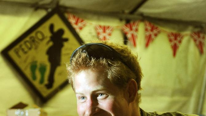 In this photo taken Nov. 3, 2012, and made available Monday Jan. 21, 2013 of Britain's Prince Harry, or just plain Captain Wales as he is known in the British Army, smiles as he plays computer games with his fellow Apache Helicopter crew, during his 12 hour VHR (very high ready-ness) shift at the British controlled flight-line in Camp Bastion southern Afghanistan. The Ministry of Defense announced Monday that the 28-year-old prince is returning from a 20-week deployment in Afghanistan, where he served as an Apache helicopter pilot with the Army Air Corps.  (AP Photo/ John Stillwell, Pool)