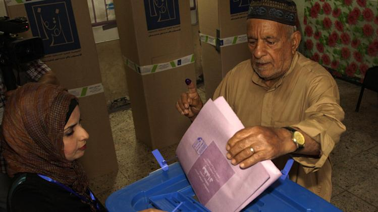 An Iraqi man casts his ballot at a polling center during the country's provincial elections in Baghdad, Iraq, Saturday, April 20, 2013.  Polls opened amid tight security in Iraq on Saturday for regional elections in the country's first vote since the U.S. military withdrawal, marking an important test of the country's stability. (AP Photo/ Khalid Mohammed)