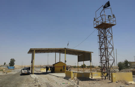 Islamic State militants stand guard after controlling a checkpoint in Khazer at the border area of the Kurdish semi-autonomous region