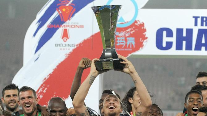Paris Saint-Germain celebrate with the trophy after winning their French season-opening Champions Trophy football match against Guingamp in Beijing on August 2, 2013