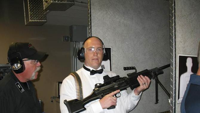 """This July 28, 2012 photo provided by Bob MacDuff shows MacDuff holding an automatic weapon at the Gun store in Las Vegas after his """"shotgun wedding."""" One Las Vegas shooting range is selling """"take a shot at love"""" packages that include 50 submachine gun rounds. Another is offering wedding packages in which the bride and groom can pose with Uzis and ammunition belts. And a third invites lovebirds to renew their vows and shoot a paper cutout zombie in the face. (AP Photo/Bob MacDuff)"""