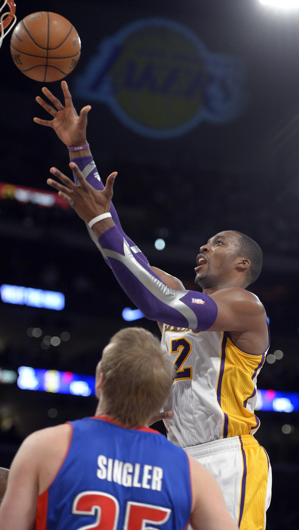 Los Angeles Lakers center Dwight Howard, right, puts up a shot as Detroit Pistons forward Kyle Singler defends during the first half of their NBA basketball game, Sunday, Nov. 4, 2012, in Los Angeles. (AP Photo/Mark J. Terrill)