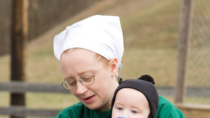 Emma Miller holds her son during a farewell picnic outside the schoolhouse in Bergholz, Ohio, Tuesday, April 9, 2013. Miller, along with three other women and a man from this tight-knit community in rural eastern Ohio, will enter prison on Friday, April 12, joining nine already behind bars on hate crimes convictions for hair- and beard-cutting attacks against fellow Amish. (AP Photo/Scott R. Galvin)