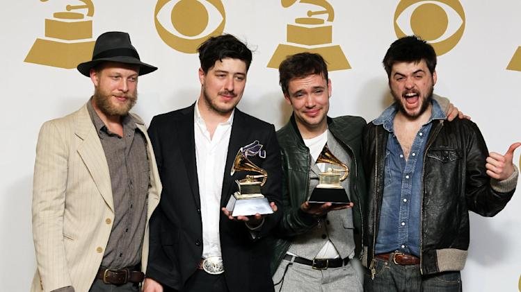 "FILE - In this Feb. 10, 2013 file photo, members of the musical group Mumford & Sons, from left, Ted Dwane, Marcus Mumford, Ben Lovett and Winston Marshall, pose backstage with the best long form music video award for ""Big Easy Express"" and the album of the year award for ""Babel"" at the 55th annual Grammy Awards in Los Angeles. The band on Thursday, June 13, 2013 announced it has canceled its headlining performance at Bonnaroo Music & Arts Festival in Tennessee. The decision comes after Dwane received treatment this week for a blood clot on his brain. (Photo by Matt Sayles/Invision/AP, File)"