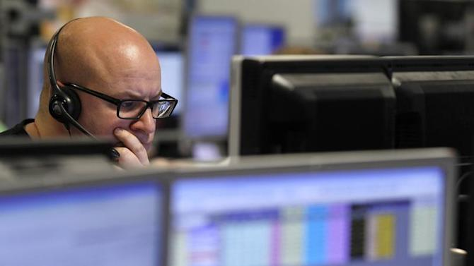 A trader monitors the screen on a trading floor in London