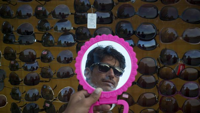 A Pakistani customer looks in a mirror as he shops for a pair of sun glasses at a vendor at the roadside in Islamabad, Pakistan, Monday, May 4, 2015. (AP Photo/B.K. Bangash)