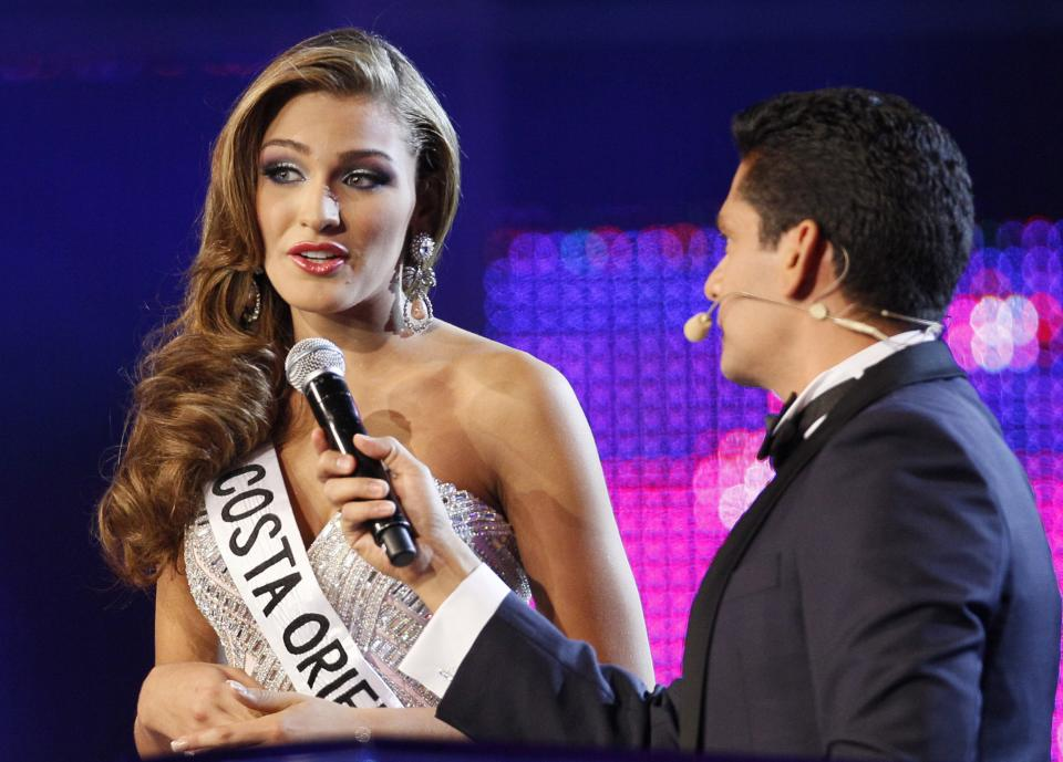 Miss Costa Oriente, Migbelis Castellanos answers a question as CNN journalist Ismael Cala listens during Miss Venezuela 2013 beauty pageant in Caracas, Venezuela, Thursday, Oct. 10, 2013. (AP Photo/Ariana Cubillos)