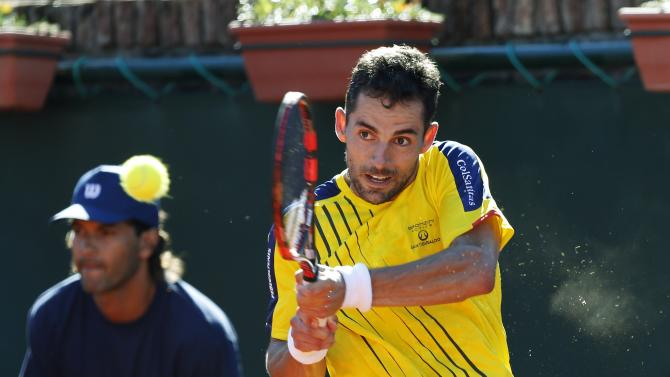 Colombia's Santiago Giraldo returns the ball to Uruguay's Martin Cuevas during their Davis Cup tennis match in Montevideo