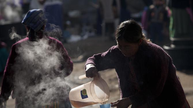 A woman pours coffee during a funeral service for the Vasquez a family who was buried alive when their house collapsed during an earthquake in San Cristobal Cucho, Guatemala, Thursday, Nov. 8, 2012.  The family died when a magnitude 7.4 earthquake struck on Wednesday, collapsing the home of the Vasquez and burying 10 of them, including a 4-year-old child, in the rubble. The powerful quake killed at least 52 people and left dozens more missing. Rescuers began employing heavy machinery early Thursday to search for more survivors. (AP Photo/Moises Castillo)