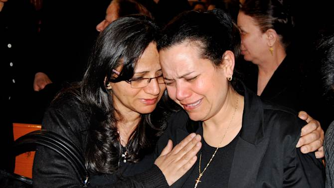"""Ragaa Abdallah, right, the wife of an Egyptian Christian who died in prison in Libya after he was detained on suspicion of having proselytized there has been buried in a subdued ceremony in his hometown, mourns during his funeral in Assuit, Egypt, Wednesday, March 13, 2012 in southern Egypt. The local church head Priest Baqi Sadaqa told the funeral congregation on Wednesday that Ezzat Atallah's death earlier this week was a """"crime against Egypt."""" (AP Photo/Mamdouh Thabet)"""