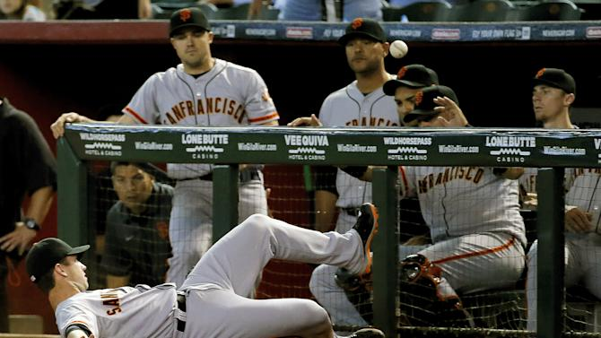 San Francisco Giants' Buster Posey can't catch a foul ball hit by Arizona Diamondbacks' Mark Trumbo in front of his dugout during the fifth inning of a baseball game, Wednesday, Sept. 17, 2014, in Phoenix. (AP Photo/Matt York)