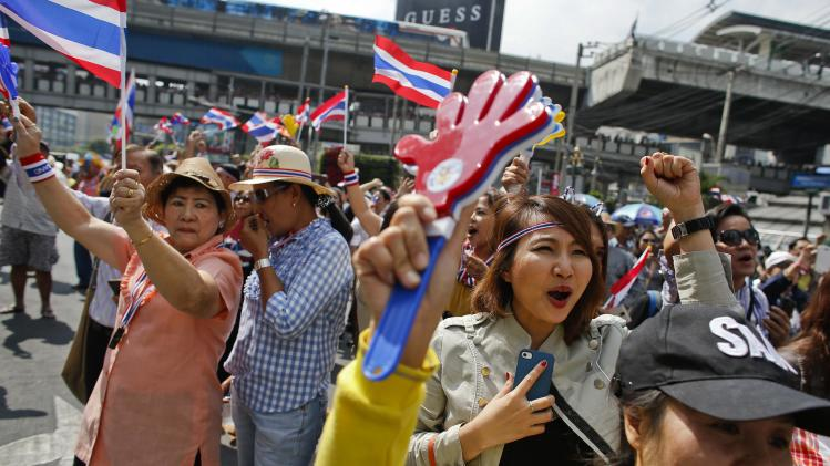Anti-government protesters shout slogans as they rally at a major business district in Bangkok