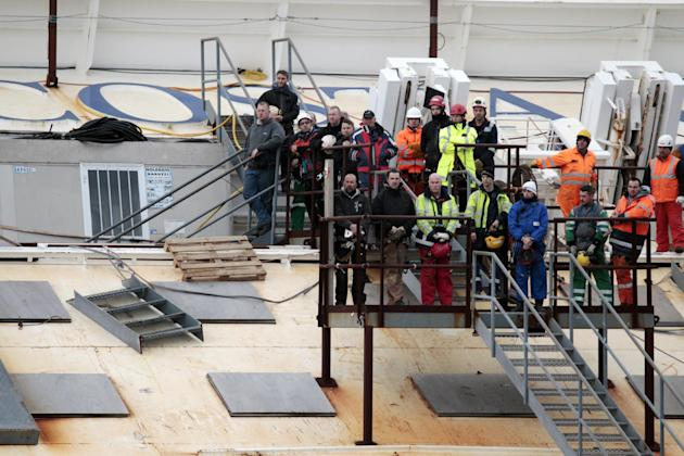 Workers observe a minute silence as they stand on the Costa Concordia cruise ship leaning on its side off the Tuscan Island Isola del Giglio, Italy, Sunday, Jan. 13, 2013. Survivors of the Costa Conco