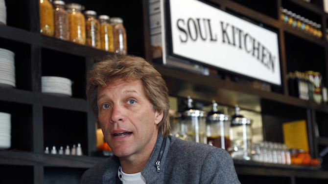 Rock star Jon Bon Jovi sits in the Soul Kitchen restaurant in Red Bank, N.J., Wednesday, Oct. 19, 2011, during the opening of the restaurant which is designed to help the hungry without the stigma of a soup kitchen. Diners pay whatever they're able to. (AP Photo/Mel Evans)