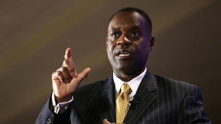 File- This Oct. 3, 2013, file photo shows Detroit Emergency Manager Kevyn Orr gesturing during an interview at the Detroit Economic Club luncheon in Detroit. A proposed plan to restructure Detroit's debt calls for retirees and pensioners to receive $4.3 billion in payments and bondholders about $1.1 billion over the next 40 years, leaving the bankrupt city with a surplus of nearly $336 million. (AP Photo/Carlos Osorio, File)