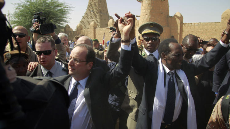 French President Francois Hollande  holds hands with Mali's interim President Dioncounda Traoré in Timbuktu, Mali, Saturday Feb. 2, 2013.(AP Photo/Jerome Delay)