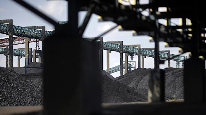 In this May 22, 2014, photo, piles of coal sit below conveyor belts at the Dominion Terminal Associates coal terminal, front, and Kinder Morgan coal terminal, back, in Newport News, Va. As the Obama administration weans the U.S. off dirty fuels blamed for global warming, energy companies have been sending more of America's unwanted energy leftovers to other parts of the world where they could create even more pollution. (AP Photo/Patrick Semansky)