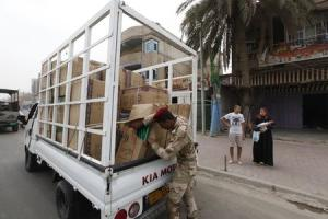 An Iraqi soldier checks goods at the back of a truck …