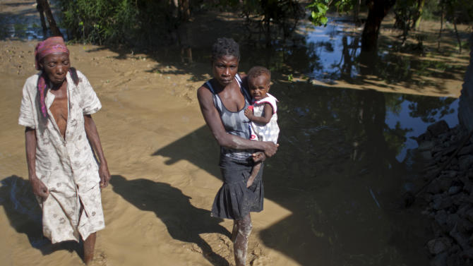 Carmene Chales, left, walks with Anes Michaelange and one-year-old Alexandra Alexandre through an area where Hurricane Sandy triggered flooding in Port-au-Prince, Haiti, Saturday, Oct. 27,  2012.  As Hurricane Sandy swirls off toward the U.S. East Coast, the Caribbean is mourning the storm-related deaths of at least 43 people and cleaning up wrecked homes, felled power lines and fallen tree branches. (AP Photo/Dieu Nalio Chery)