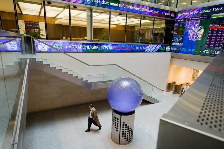 People walk in the foyer of the London Stock Exchange in central London on March 7, 2013
