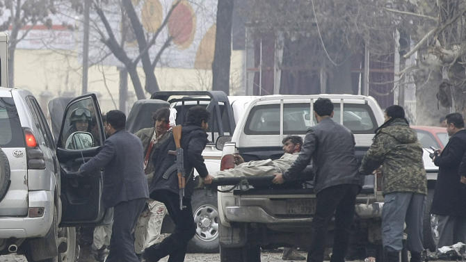 Afghans load a victim, right, into an ambulance at the scene of a suicide car bomb attack in Kabul, Afghanistan, Wednesday, Jan. 16, 2013. Six militants — one driving a car packed with explosives — attacked the gate of the Afghan intelligence service in the capital Kabul on Wednesday, setting off a blast that could be heard throughout downtown and which sent a plume of dark smoke rising into the sky. (AP Photo/Musadeq Sadeq)