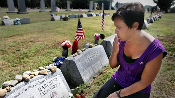 Patty DiRenzo puts her hand to her face to give a kiss to her son, Salvatore Marchese's grave, Monday, July 16, 2012, in Blackwood, NJ.  DiRenzo's son died of a drug overdose on Sept. 23, 2010 and she is now a part of a nationwide push to make sure people won't be afraid of being arrested on drug possession charges to call 911 when someone has overdosed.  (AP Photo/Brynn Anderson)