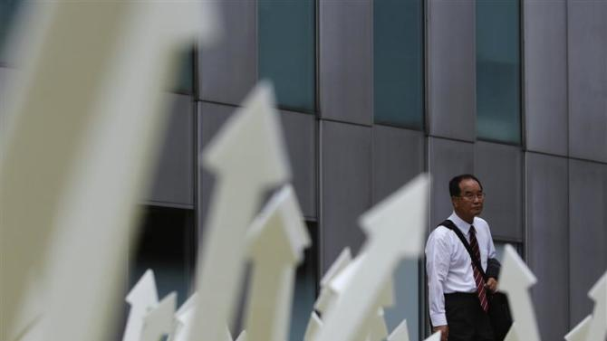 A man walks past an artwork displayed in Tokyo's business district