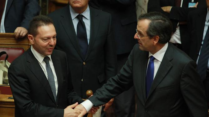 Greece's Prime Minister Antonis Samaras, right, shakes hands with Finance Minister Yannis Stournaras after a vote for the new austerity measures at the Greek parliament in Athens, Wednesday, Nov. 7, 2012. Greek lawmakers have narrowly passed a crucial austerity bill by majority vote, but with heavy dissent from within the three-party governing coalition. (AP Photo/Thanassis Stavrakis)