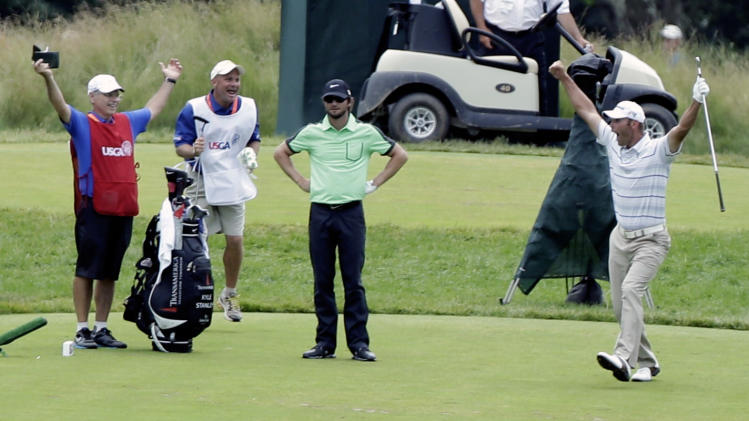 Shawn Stefani, right, reacts after hitting a hole in one on the 17th hole as Kyle Stanley looks on during the fourth round of the U.S. Open golf tournament at Merion Golf Club, Sunday, June 16, 2013, in Ardmore, Pa. (AP Photo/Julio Cortez)
