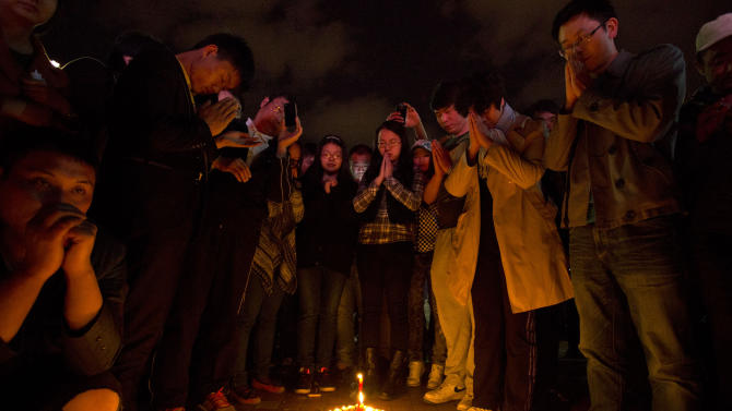 People light up candles and pray for the victims on a square outside the Kunming Railway Station where more than 10 assailants slashed scores of people with knives the night before in Kunming, in western China's Yunnan province, Sunday, March 2, 2014. Authorities blamed a slashing rampage that killed 29 people and wounded 143 at a train station in southern China on separatists from the country's far west and vowed a harsh crackdown Sunday, while residents wondered why their laid-back city was targeted. (AP Photo/Alexander F. Yuan)