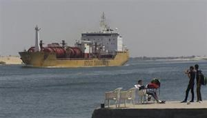 People are seen near ship crosses the Suez Canal near Ismailia port city, 120 km northeast of Cairo