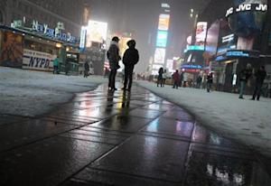 People stand on a heated section of pavement as it snows in Times Square in New York