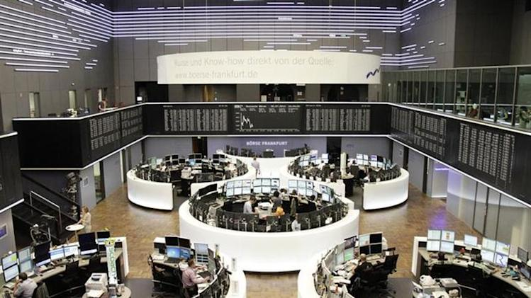 Traders are pictured at their desks in front of the DAX board at the Frankfurt stock exchange July 5, 2013. REUTERS/Remote/Stringer/Files