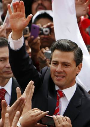 FILE - In this Nov. 27, 2011 file photo, Enrique Pena Nieto, former governor of Mexico state and presidential candidate for the Institutional Revolutionary Party, PRI, waves to supporters during a rally in Mexico City.  Pena Nieto, the leading contender for Mexico's presidency, has raised criticism for his inability to name three books that influenced him during a book fair over the weekend of Dec 3-4.  (AP Photo/Marco Ugarte, File)