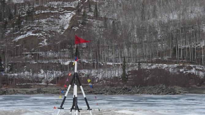FILE - In this Thursday, April 12, 2012 file photo, a red flag is whipped by wind on a tripod sitting on the frozen Nenana River on, in Nenana, Alaska. The tripod serves as the basis for Alaska's biggest guessing game, with people buying tickets to guess when the ice will give out and the tripod will fall into the river. That happened at 7:39 p.m. Monday night, April 23, 2012.  Ice Classic officials will contact the winners when all of the tickets have been entered.  She says that could take another week or so.  (AP Photo/Mark Thiessen)