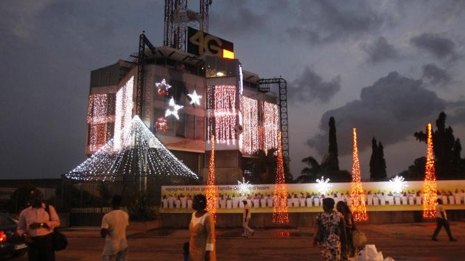 People stand next to a building decorated with lights in the Marcory area in Abidjan