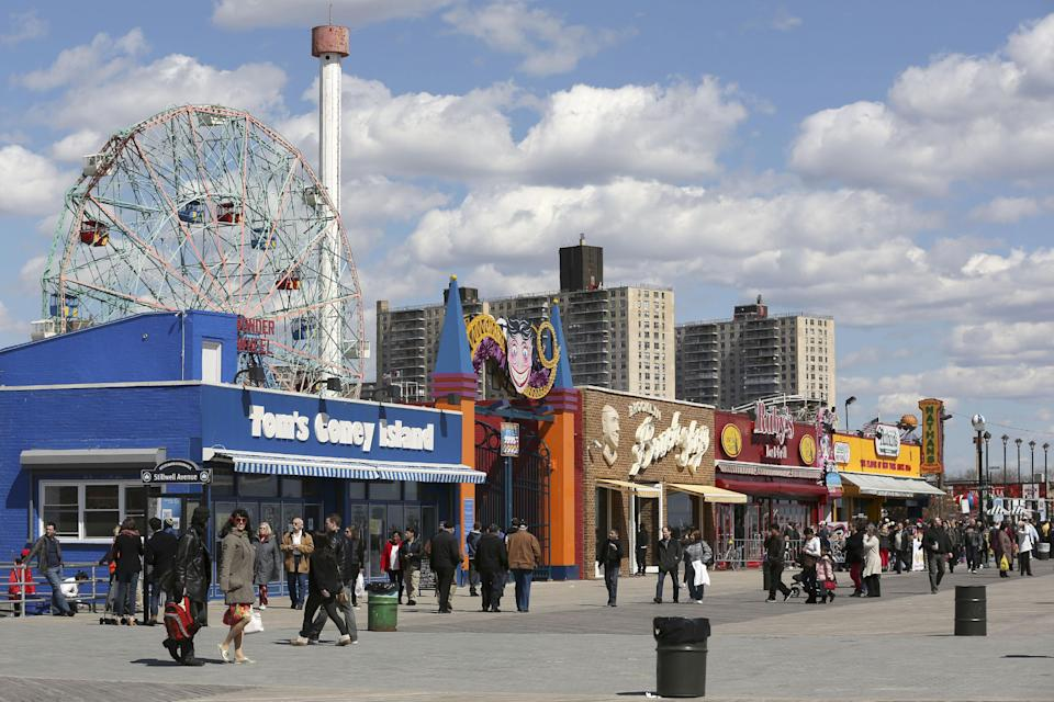 In a Saturday March 30, 2013, photo visitors to New York's Coney Island walk on the boardwalk past the open businesses. Despite making the traditional Palm Sunday opening, many of the seasonal businesses at Coney Island are still reeling from the aftermath of Superstorm Sandy. (AP Photo/Mary Altaffer)