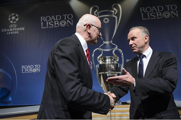 Arsenal club secretary David Miles, left, shakes hands with Bayern Munich CEO Karl-Heinz Rummenigge, right, after the draw of the round of 16 games of UEFA Champions League 2013/14 at the UEFA Headqua