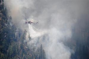 A water-dropping helicopter makes its delivery at the Slide Fire in Oak Tree Canyon near Sedona, Arizona