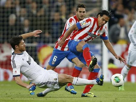 Real Madrid's Xabi Alonso challenges Atletico Madrid's Radamel Falcao during their Spanish King's Cup final soccer match at Santiago Bernabeu stadium in Madrid