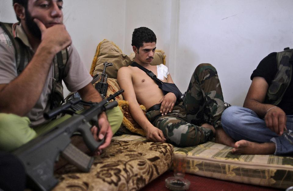 Syrian rebel fighter, Mohammed Adnan, 21, center, who was shot in the shoulder by a government sniper on Saturday while fighting in Aleppo, rests with other fighters at their headquarters in Suran, on the outskirts of Aleppo, Syria, Sunday, Sept. 9, 2012. (AP Photo/Muhammed Muheisen)