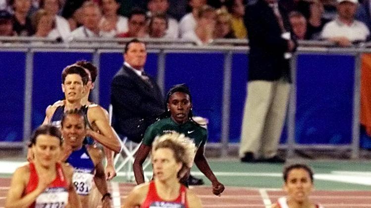 U.S. runner Suzy Favor Hamilton falls during the women's 1,500 meter final at the Summer Olympics Saturday, Sept. 30, 2000, at Olympic Stadium in Sydney. Gold medal winner Nouria Merah-Benida of Algeria is at right. (AP Photo/Rusty Kennedy)