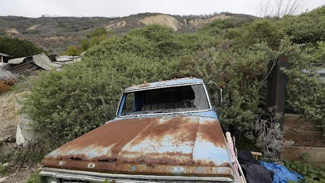 A rusted Ford pickup truck remains buried by a mudslide in the tiny coastal town of La Conchita, Calif., Monday, March, 24, 2014. As with Oso, Wash., the coastal Southern California town of La Conchita knows the sorrows that a major mudslide can unleash. In 2005, a wall of debris slammed down from a bluff soaked by winter storms, killing 10 people and damaging or destroying 36 homes. (AP Photo/Damian Dovarganes)