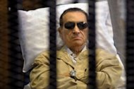 Ousted Egyptian president Hosni Mubarak sits inside a cage in a courtroom during his verdict hearing in Cairo on June 2, 2012. A retrial of the former president is to open on April 13, Egypt's official MENA news agency reported on Sunday.